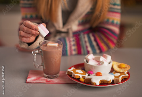Closeup on girl putting marshmallow into cup of hot chocolate