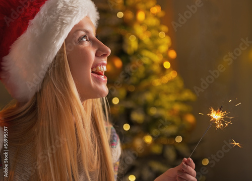 Profile portrait of teenage girl in santa hat holding sparklers