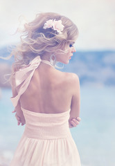 Gorgeous blonde in white dress on the beach
