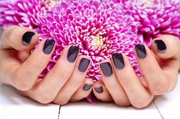 Closeup fingernails with dark fashion manicure and flowers