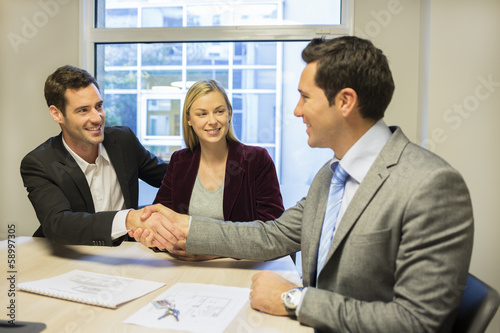 Couple meeting with financial adviser, handshake