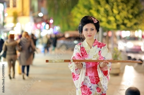 Japanese geisha samurai with sword outside at night
