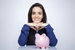 Happy smiling woman and a piggy bank against gray background