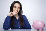 Happy smiling woman looking to a piggy bank against gray backgro