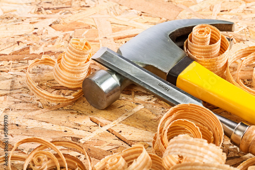 claw hammer and carpenter chisel with wooden chips