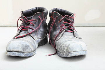 pair of old dirty work boots in building site