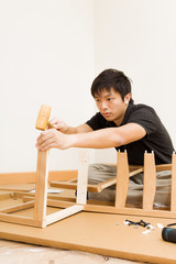 Asian man assembling chair by hammer