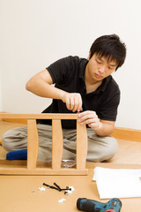 Asian man assembling chair at home