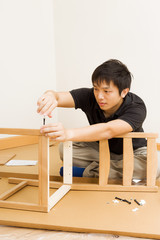 Asian man assembling chair at home