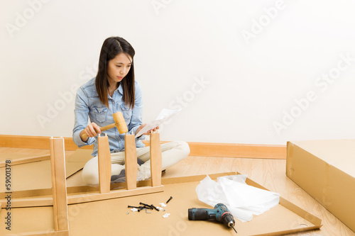Asian woman follow instruction for assembling chair
