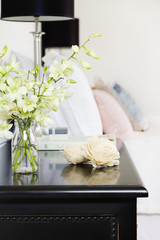 Orchids in vase on pretty bedside table vertical