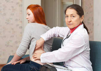 Mature physician touching  behind of  patient