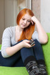 Red-haired  teenager girl waits telephone call