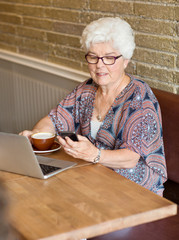 Woman Text Messaging Through Smartphone In Cafe