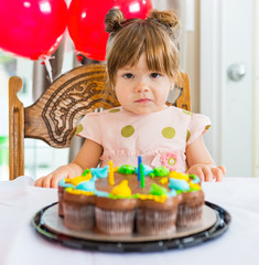 Girl Sitting In Front Of Birthday Cake