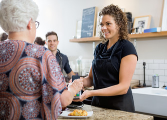 Woman Paying Through Smartphone At Cafe