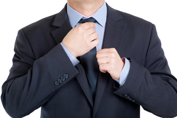 Close-up of a businessman adjusting his tie