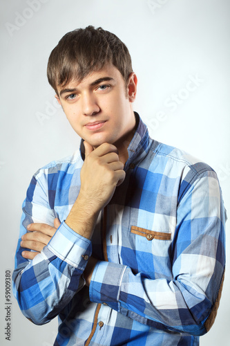 Portrait of casual young man looking at camera with arms crossed