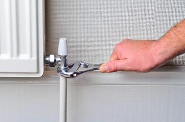Plumber repairing a radiator pipe
