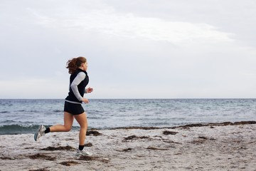 Young female athlete jogging on beach