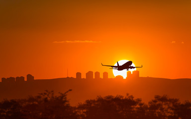 passenger plane take off runway from airport at sunset