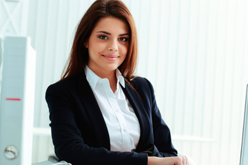 Young beautiful happy businesswoman sitting