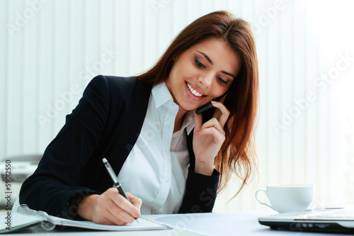 Young happy businesswoman talking on the phone