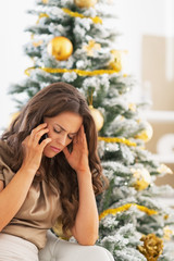 Frustrated young woman talking mobile phone near christmas tree