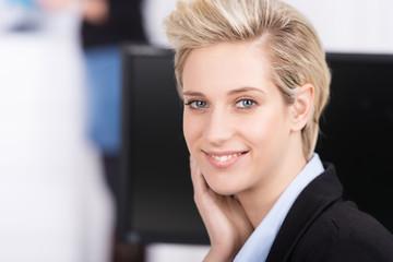 lächelnde blonde geschäftsfrau am arbeitsplatz