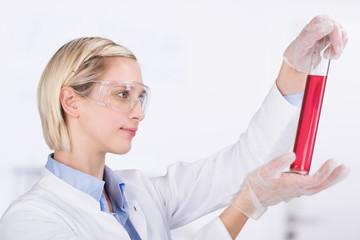 chemielaborantin schaut auf rote flüssigkeit