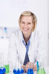 lachende junge frau mit kittel im labor