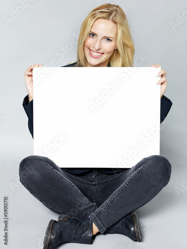 Woman presenting blackboard with copyspace