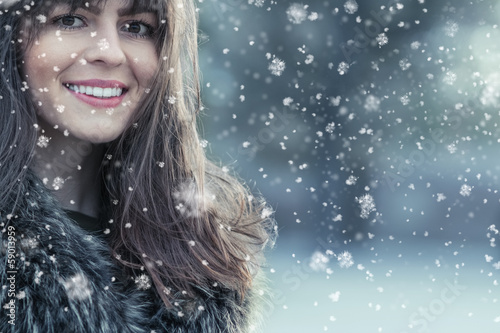 Portrait of a smile young woman in a winter snow day
