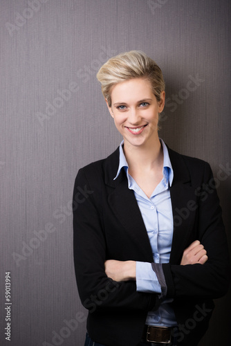 lächelnde mitarbeiterin mit verschränkten armen