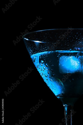 detail of half glass of fresh blue cocktail on black background