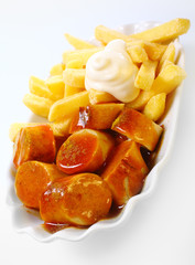 Crisp fried potato chips with spicy Currywurst