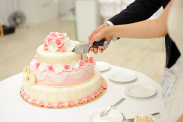bride and groom cutting elegant cake with roses