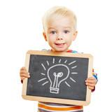 Fototapety Kind hält Tafel mit Glühbirne