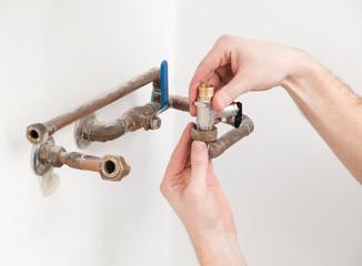 Hands repairing plumbing pipes