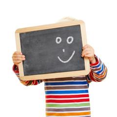 Kind hält Tafel mit Smiley vor Gesicht