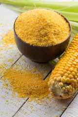 Corn cob and corn meal on wooden background