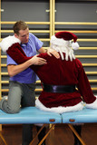 male therapist massaging stressed Santa Claus in fitness studio