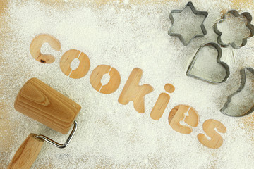"Stencil word ""cookies"" made with flour on wooden table"