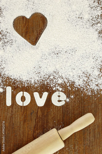 "Stencil word ""love"" made with flour on wooden table"