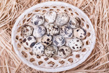 Quail eggs in a wicker basket with straw , top view