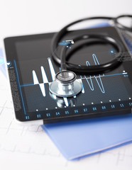 tablet pc, stethoscope and electrocardiogram