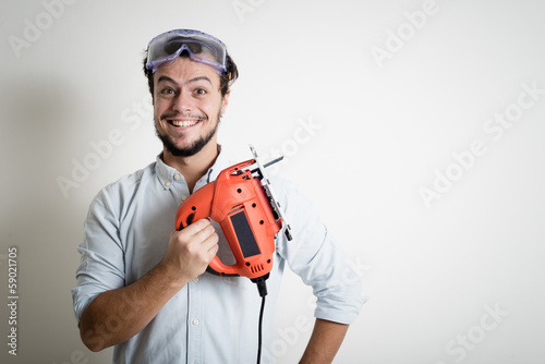 young man bricolage working with electric saw