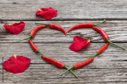 Red chili peppers in a heart shape with rose-petals