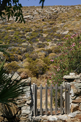 Fence gate leading to rugged, rocky hill