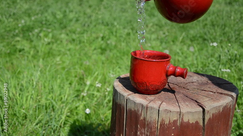 woman hand holding the clay jar pour water small pretty cup